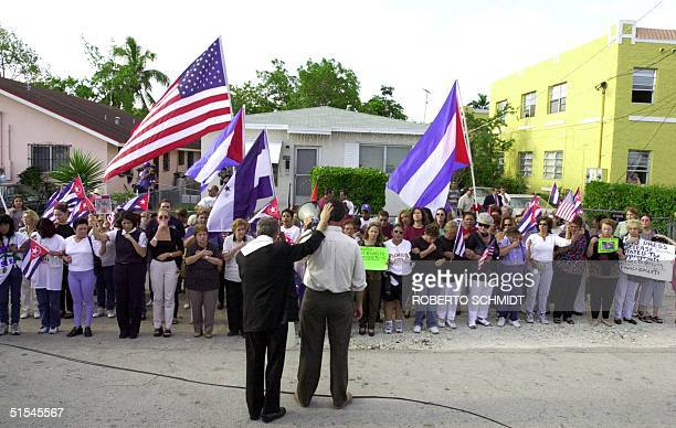 CubanAmerican women listen to Ramon Saul Sanchez as he instructs them in making a human chain around Elian Gonzalez'z Miami relative's home after the...