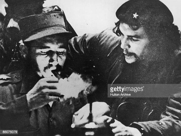 Cubanrevolutionary Fidel Castro lights his cigar while Argentine revolutionary Che Guevara looks on in the early days of their guerrilla campaign in...