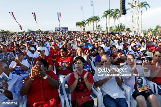Cubans applaud during a political act at the Plaza de la Revolucion to celebrate the 50th anniversary of the death of Ernesto Che Guevara on October...