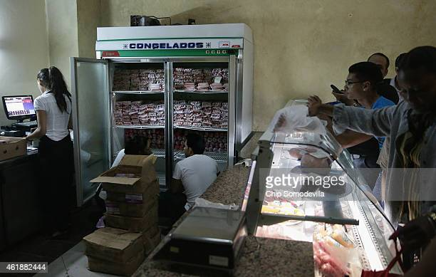 Cubans belly up to a refridgerator to purchase frozen hot dogs and ground beef at a store in the Habana Vieja neighborhood January 20 2015 in Havana...