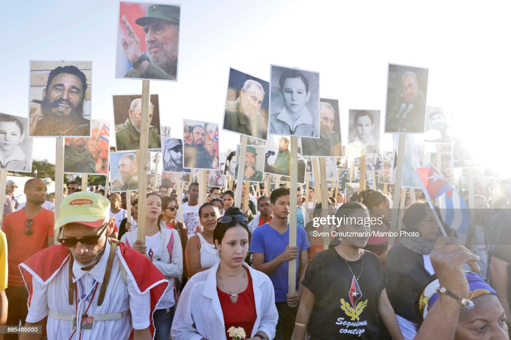 Cubans carry photos of late Cuban Revolution leader Fidel Castro during a march from the Revolution square to the Santa Ifigenia cemetery, as Cuba commemorates the first anniversary of Castros funeral, on December 4, 2017 in Santiago de Cuba. Castro died on November 25, 2016 and his remains were buried on December 4th, 2016, after spending one night at the Revolution square, in Santiago de Cuba. Cuba will hold elections in February who will define the successor of Cubas President, Raul Castro.