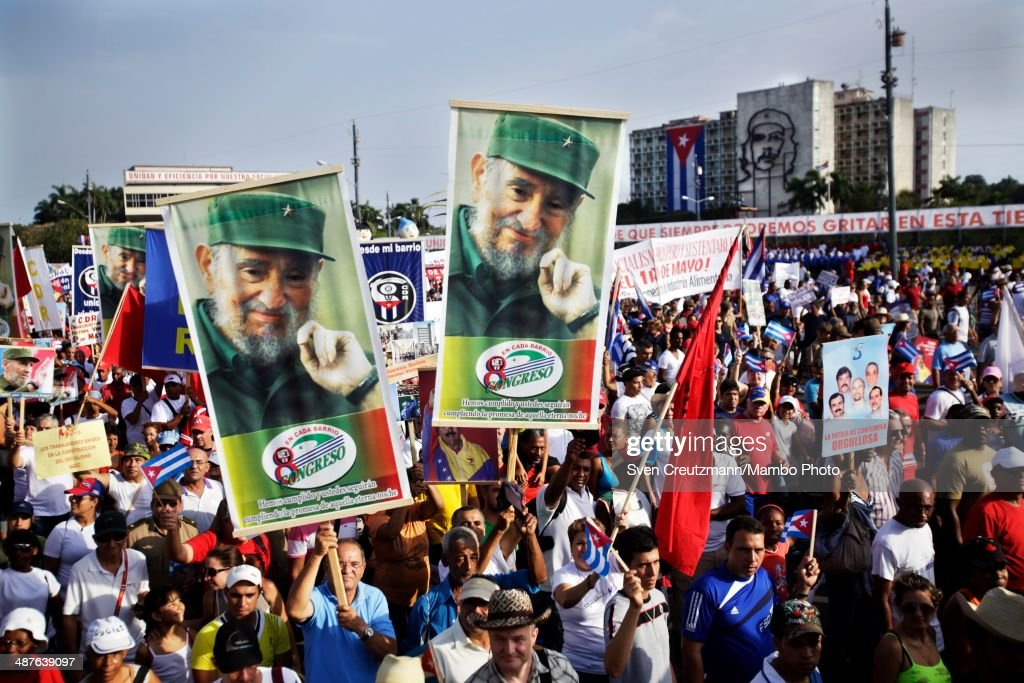Cubans carry the image of Cuba's Revolution leader Fidel Castro as they walk in front of Cuba's Ministry of Interior bearing the image of Che Guevara...
