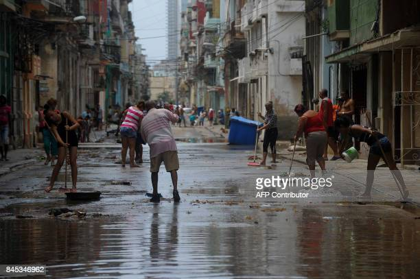Cubans clean a street of Havana on September 10 2017 Deadly Hurricane Irma battered central Cuba on Saturday knocking down power lines uprooting...