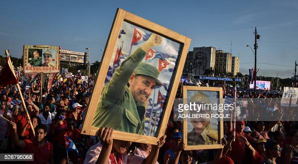 TOPSHOT Cubans display pictures of Cuban former president Fidel Castro and president Raul Castro during the May Day parade in Havana on May 1 2016 /...