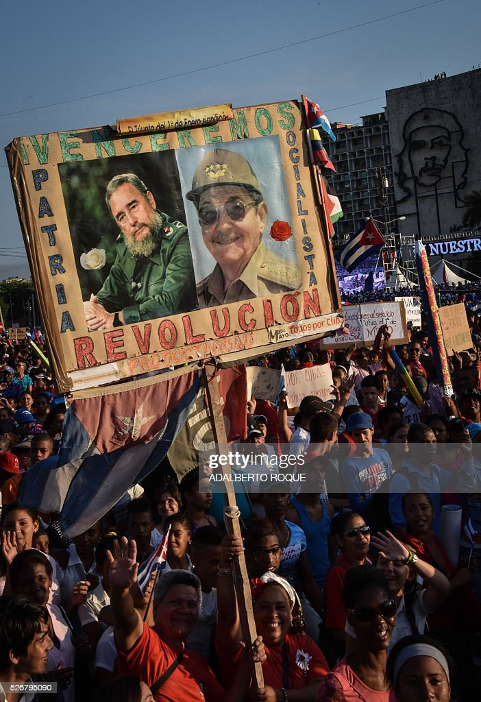 Cubans display pictures of Cuban former president Fidel Castro and president Raul Castro (R) during the May Day parade in Havana, on May 1, 2016. / AFP / ADALBERTO