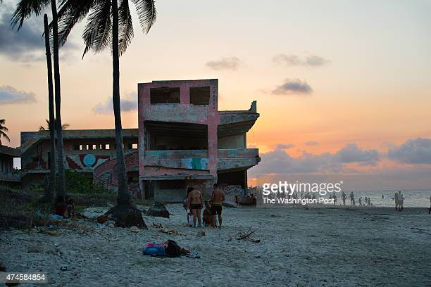 Cubans enjoy a warm April evening in the seaside beach town of Guanabo which is about 20 miles East of Havana An abandoned low rise hotel sits on the...