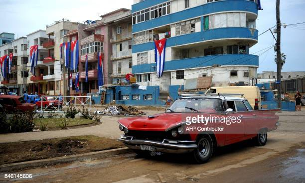 Cubans flags are hung from balconies to dry during the cleanup ensuing the passage of Hurricane Irma in Havana on September 12 2017 / AFP PHOTO /...