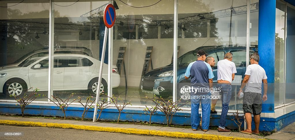 Cubans garter to watch new and used cars for sale at a car dealer in Havana on January 3, 2014. The free sale of cars in Cuba has been officially authorized Friday, but at astronomical prices. AFP PHOTO/ADALBERTO ROQUE