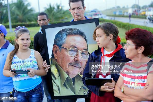 Cubans hold a picture of Cubas President Raul Castro as waiting for the caravan carrying the remains of Revolution leader Fidel Castro on the third...