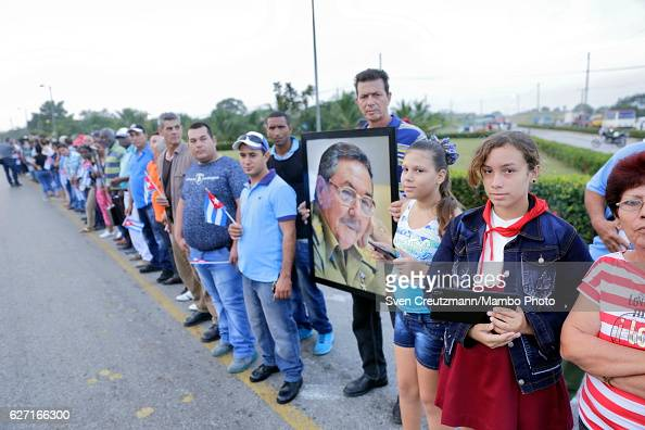 Cubans hold a picture of Cuba`s President Raul Castro as waiting for the caravan carrying the remains of Revolution leader Fidel Castro on the third...