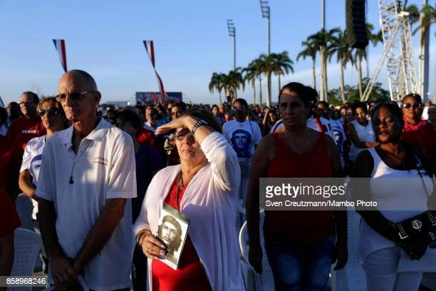 Cubans hold images of Che Guevara prior to a political act at the Plaza de la Revolucion to celebrate the 50th anniversary of the death of Ernesto...