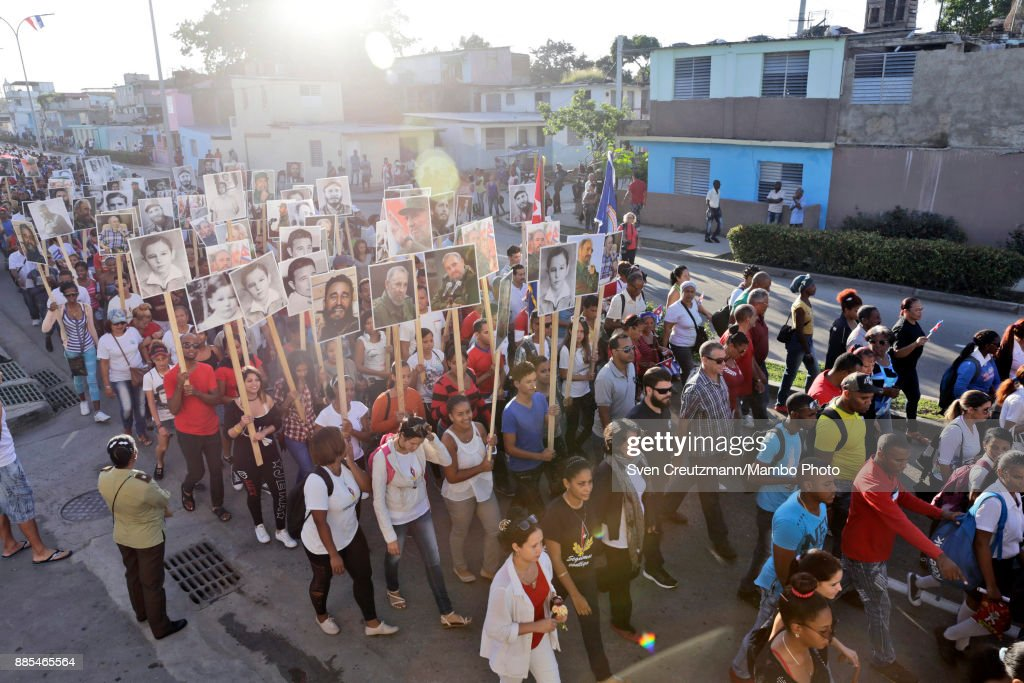 Cubans hold photos of late Cuban Revolution leader Fidel Castro during a march from the Revolution square to the Santa Ifigenia cemetery, as Cuba commemorates the first anniversary of Castros funeral, on December 4, 2017 in Santiago de Cuba. Castro died on November 25, 2016 and his remains were buried on December 4th, 2016, after spending one night at the Revolution square, in Santiago de Cuba. Cuba will hold elections in February who will define the successor of Cubas President, Raul Castro.