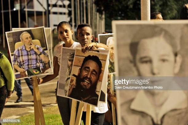 Cubans hold photos of late Cuban Revolution leader Fidel Castro at the Revolution square prior to a march towards the cemetery as Cuba commemorates...