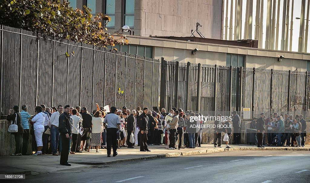 Cubans line up in front of the United States Interests Section (SINA) in Havana to get the visa to travel to the U.S. on March 11, 2013. After years of being denied the right to leave their country, the Cuban dissidents began to travel in numbers around the world to spread their ideas and to seek for support. AFP PHOTO/ADALBERTO ROQUE
