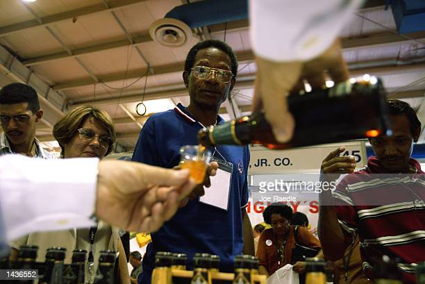 Cubans line up to taste New Amsterdam Ale from New York during the US Food Agribusiness Exhibition September 28 2002 in Havana Cuba The exhibition is...