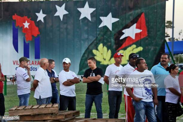 Cubans line up under an image that depicts Fidel Castros insignias prior to a political act at the Plaza de la Revolucion to celebrate the 50th...