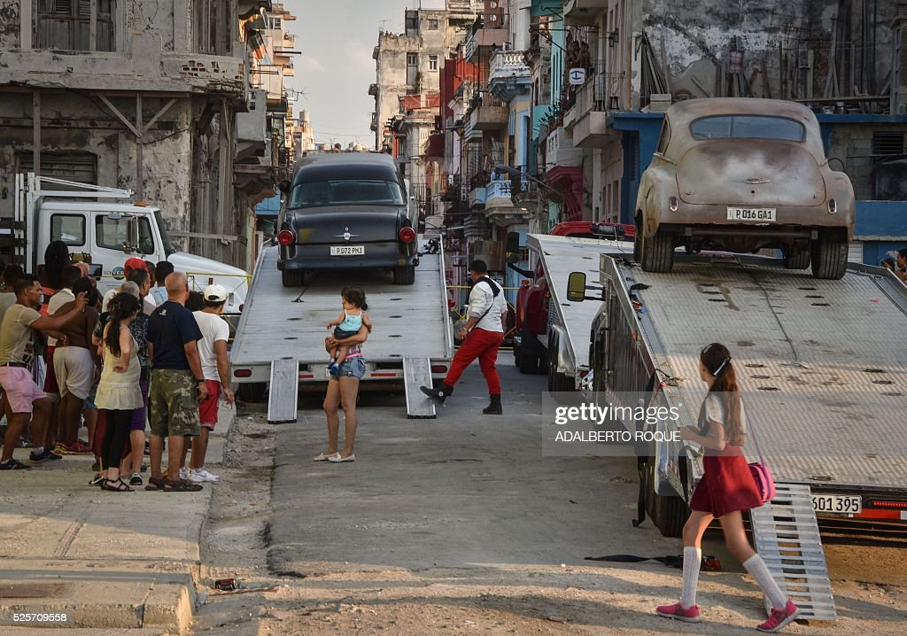 Cubans look at cars used during the shooting of Fast & Furious 8 in Havana, on April 28, 2016. / AFP / ADALBERTO