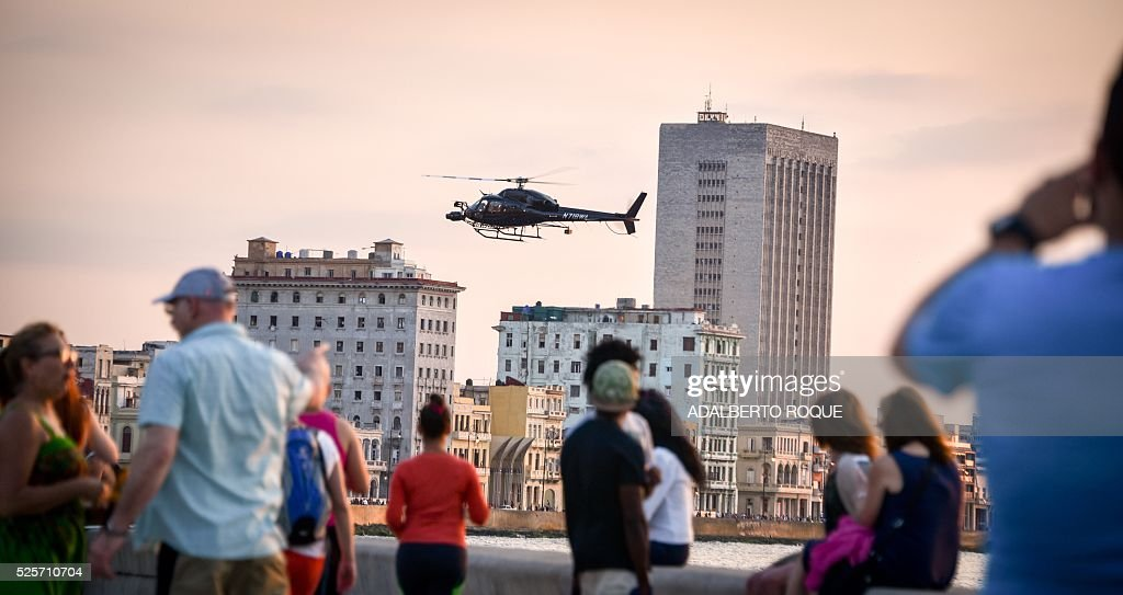 Cubans look at one of the helicopters from Universal Studios of Hollywood used during the shooting of Fast & Furious 8 in Havana, on April 28, 2016. / AFP / ADALBERTO