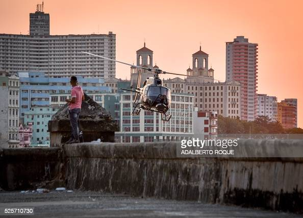 TOPSHOT Cubans look at one of the helicopters from Universal Studios of Hollywood used during the shooting of Fast Furious 8 in Havana on April 28...