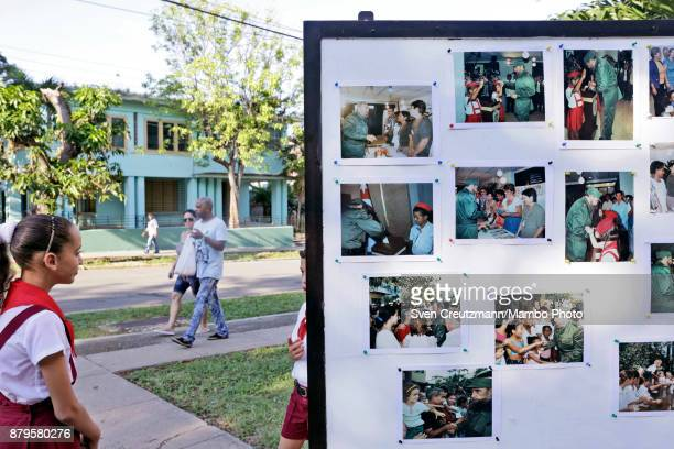 Cubans look at photos of late Revolution leader Fidel Castro at the premise where Castro used to cast his vote on occasion of municipal elections...