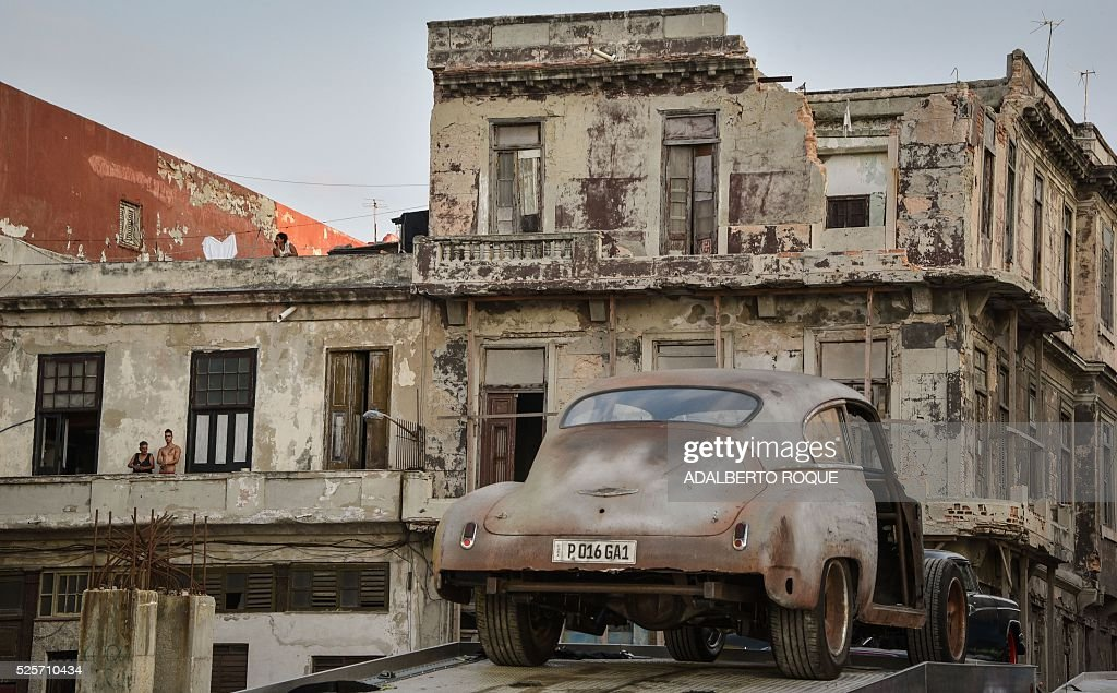 Cubans looks at one of the cars used during the shooting of Fast & Furious 8 in Havana, on April 28, 2016. / AFP / ADALBERTO