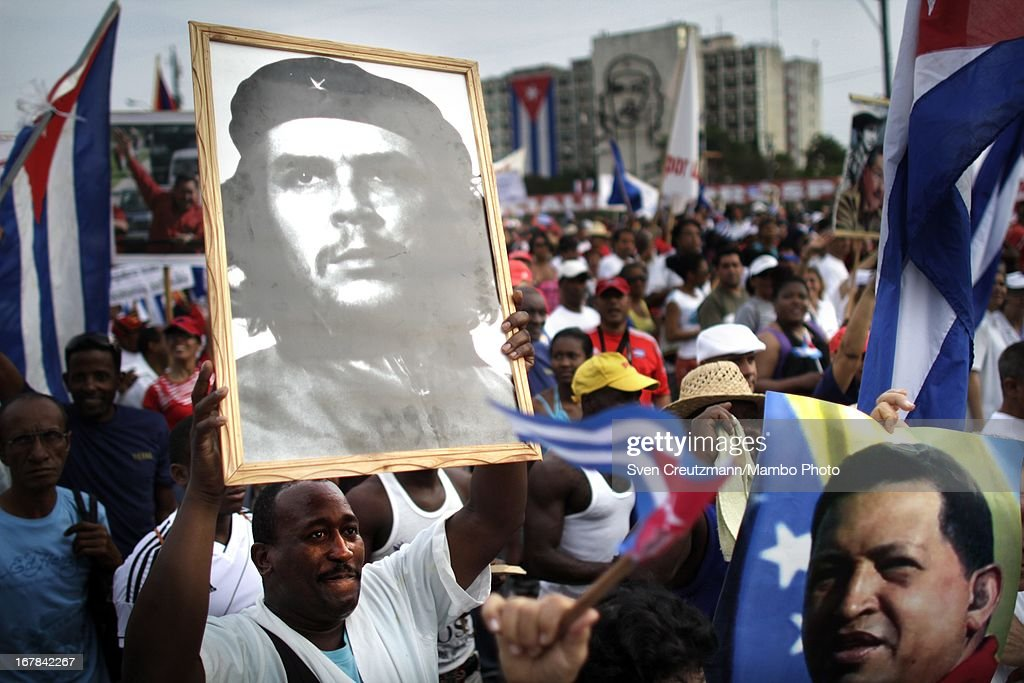 Cubans march holding images of late Venezuelan President Hugo Chavez (R) and Che Guevara (L) during the annual May Day parade of hundreds of Cubans at the Revolution Square on May 1, 2013 in Havana, Cuba. Former president Fidel Castro last attended a May Day parade in 2006, before he fell ill, just two months later.