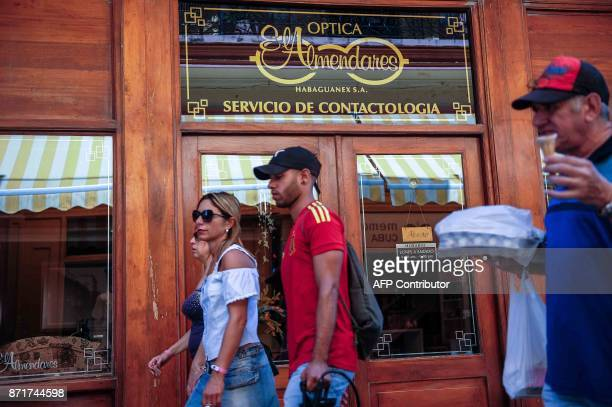 Cubans pass in front of a ophthalmology store property of Habaguanex Corporation in Havana on November 8 2017 Tighter restrictions on US travellers...