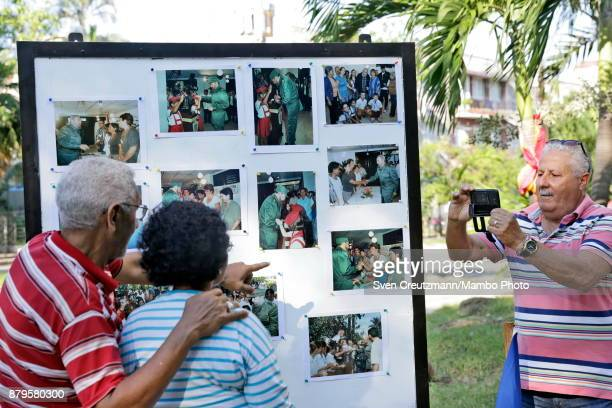 Cubans pose in front of a wall with photos of late Revolution leader Fidel Castro at the premise where Castro used to cast his vote on occasion of...