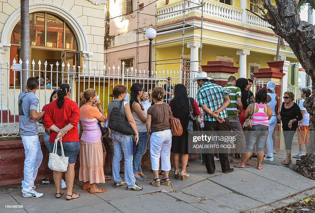 Cubans queue outside a Migrations Office to request new passport, on January 14, 2013 in Havana. A law allowing Cubans to travel abroad without special exit visas took effect on the communist-ruled island for the first time in half a century. The measure does away with the exit visas that have kept most Cubans from ever traveling abroad. AFP PHOTO/ADALBERTO ROQUE