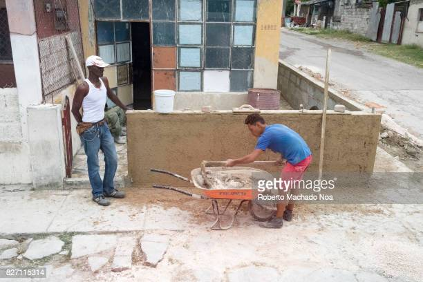 Cubans repairing a house Man mixing cement in small wheelbarrow in front of house with coloured glass in the facade