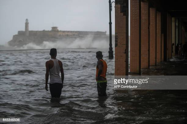Cubans stand in a flooded street in Havana on September 10 2017 Deadly Hurricane Irma battered central Cuba on Saturday knocking down power lines...