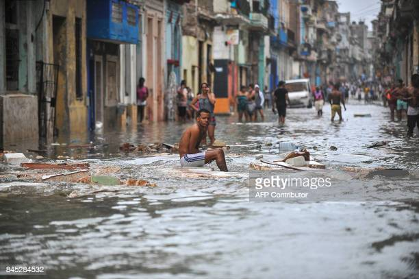 Cubans stay in a flooded street in Havana on September 10 2017 Deadly Hurricane Irma battered central Cuba on Saturday knocking down power lines...