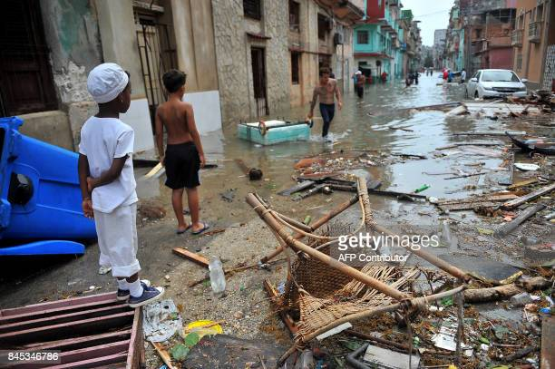 Cubans stay on a street full of debris in Havana on September 10 2017 Deadly Hurricane Irma battered central Cuba on Saturday knocking down power...