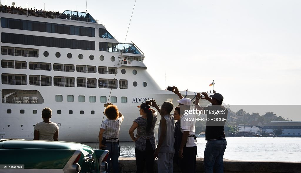 Cubans take pictures as the first US-to-Cuba cruise ship to arrive in the island nation in decades glides into the port of Havana, on May 2, 2016. The first US cruise ship bound for Cuba in half a century, the Adonia -- a vessel from the Carnival cruise's Fathom line -- set sail from Florida on Sunday, marking a new milestone in the rapprochement between Washington and Havana. The ship -- with 700 passengers aboard -- departed from Miami, the heart of the Cuban diaspora in the United States. / AFP / ADALBERTO