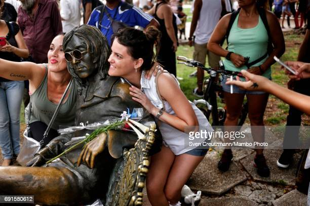 Cubans take selfies next to a bronze statue of John Lennon during a concert in tribute to the Beatles on occasion of the 50th anniversary of the Sgt...