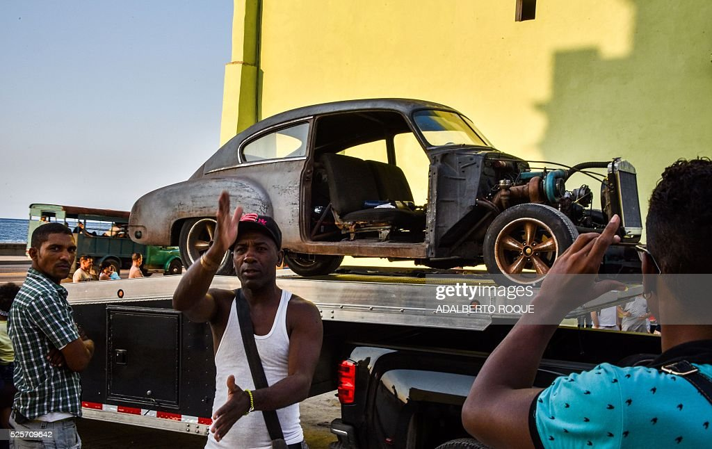 Cubans take snapshots of cars used during the shooting of Fast & Furious 8 in Havana, on April 28, 2016. / AFP / ADALBERTO