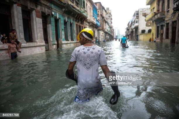 TOPSHOT Cubans wade through a flooded street in Havana on September 10 2017 Deadly Hurricane Irma battered central Cuba on Saturday knocking down...