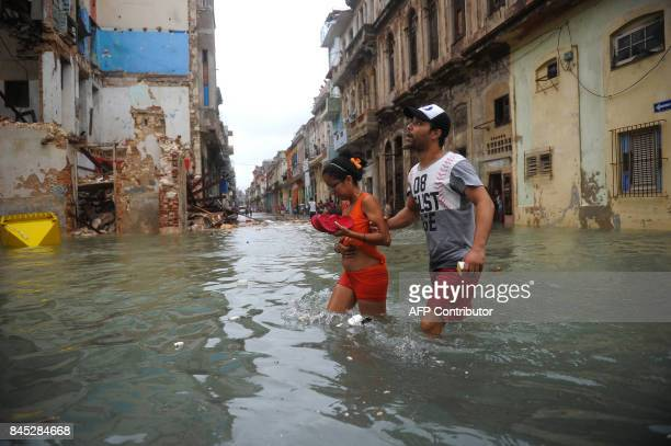 Cubans wade through a flooded street in Havana on September 10 2017 Deadly Hurricane Irma battered central Cuba on Saturday knocking down power lines...