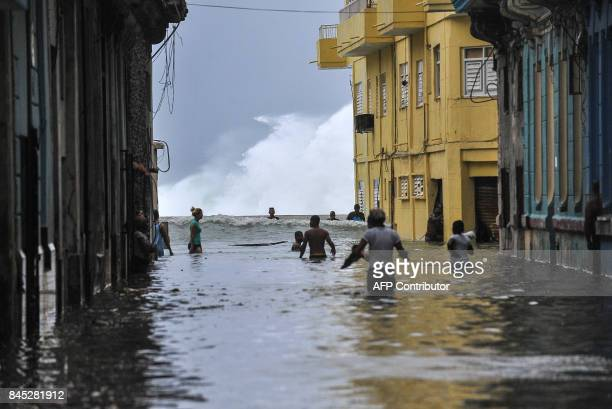 Cubans wade through a flooded street near the Malecon in Havana on September 10 2017 Deadly Hurricane Irma battered central Cuba on Saturday knocking...
