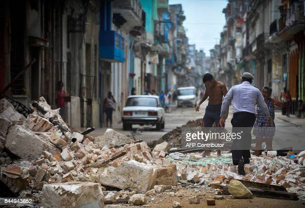 Cubans wade through the rubble from a collapsed building in Havana on September 9 2017 Irma's blast through the Cuban coastline weakened the storm to...