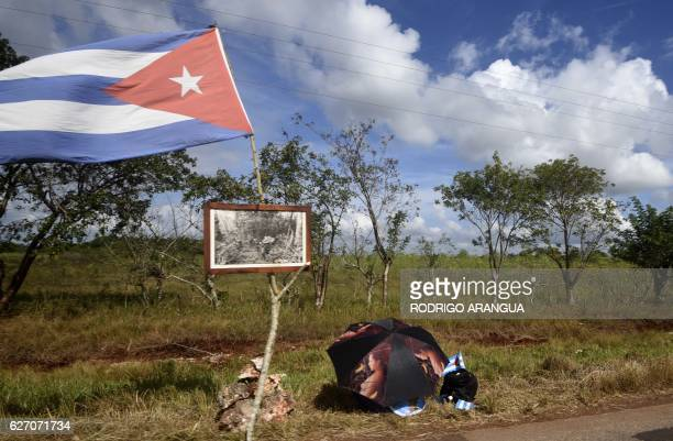 Cubans wait for the passage of the convoy carrying the remains of Cuban revolutionary leader Fidel Castro at the Carretera Central on December 1 2016...