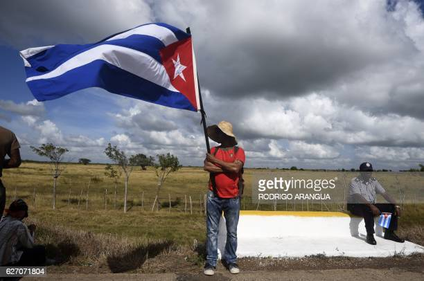 TOPSHOT Cubans wait for the passage of the convoy carrying the remains of Cuban revolutionary leader Fidel Castro at the Carretera Central on...