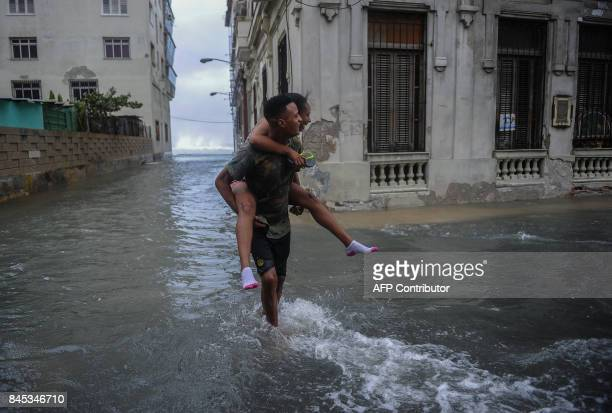 Cubans walk along a flooded street in Havana on September 10 2017 Deadly Hurricane Irma battered central Cuba on Saturday knocking down power lines...