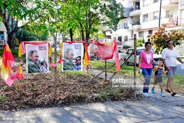 Cubans walk past photos of late Revolution leader Fidel Castro as they arrive to cast their vote at premise where Castro used to cast his vote on...