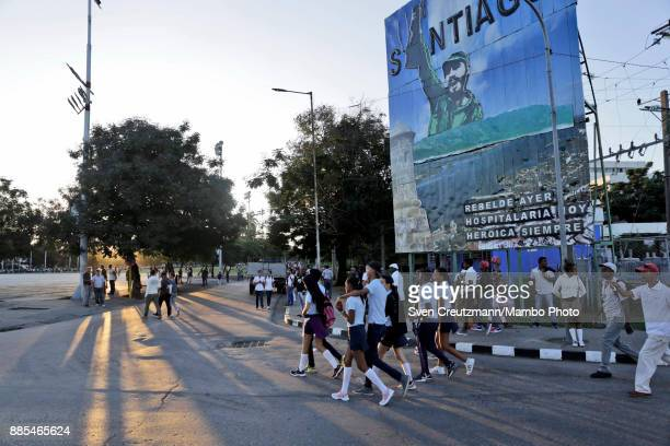Cubans walk under a neon sign with the photo of late Cuban Revolution leader Fidel Castro at the Revolution square prior to a march towards the...