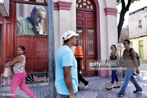 Cubans walk under a photo of late Cuban Revolution leader Fidel Castro as Cuba commemorates the first anniversary of Castro's funeral on December 3...