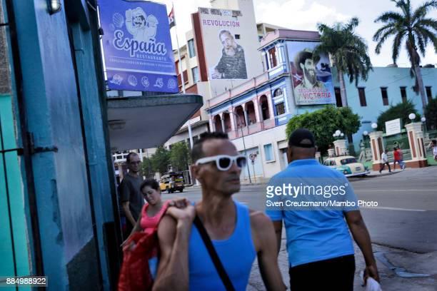 Cubans walk under photos of late Cuban Revolution leader Fidel Castro and Commander Camilo Cienfuegos as Cuba commemorates the first anniversary of...