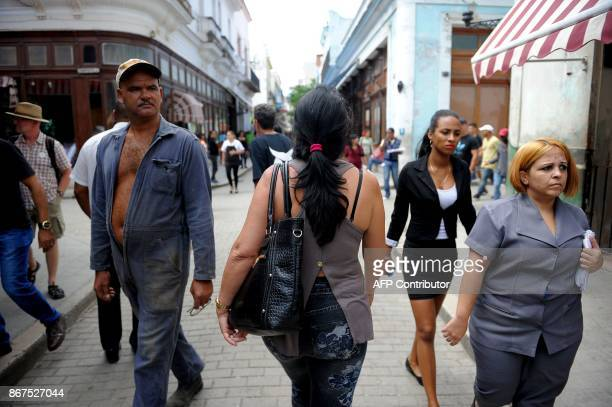 Cubans walks along a street of Havana on October 27 2017 Almost drowned by the crisis of the 90s the emerging Cuban fashion begins to thrive boosted...