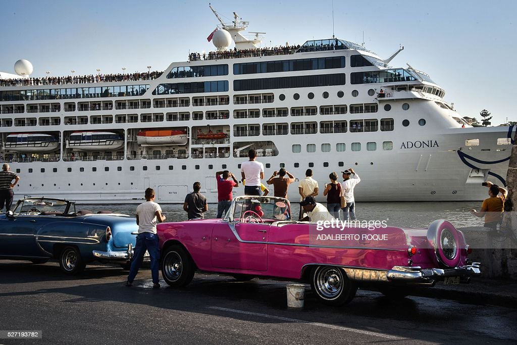Cubans watch as the first US-to-Cuba cruise ship to arrive in the island nation in decades glides into the port of Havana, on May 2, 2016. The first US cruise ship bound for Cuba in half a century, the Adonia -- a vessel from the Carnival cruise's Fathom line -- set sail from Florida on Sunday, marking a new milestone in the rapprochement between Washington and Havana. The ship -- with 700 passengers aboard -- departed from Miami, the heart of the Cuban diaspora in the United States. / AFP / ADALBERTO
