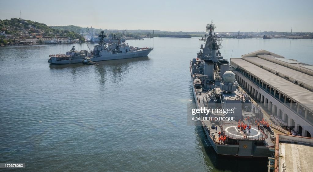 Cubans watch as the 'Moskva' Russian guide missile cruiser (R) and destroyer ' Vice Admiral Kulakov' (L) moor at Havana's harbour, on August 3, 2013. The vessel is part of a three-ship group in official visit to Cuba. AFP PHOTO/Adalberto ROQUE